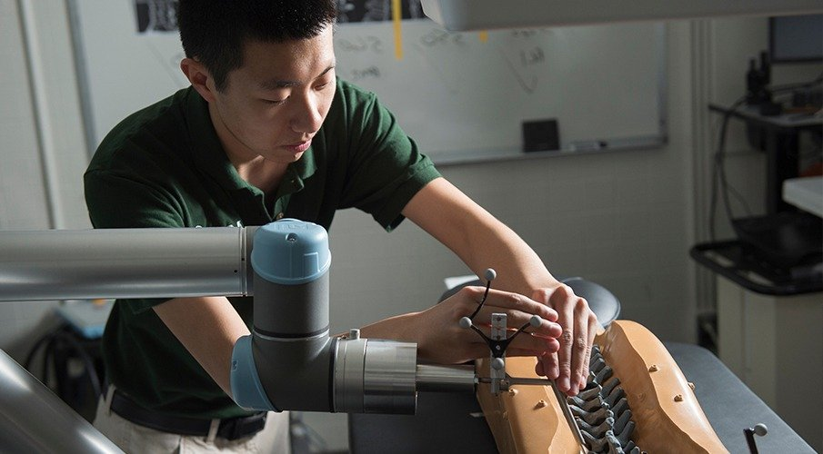 Male student working with a robotic arm in the lab.