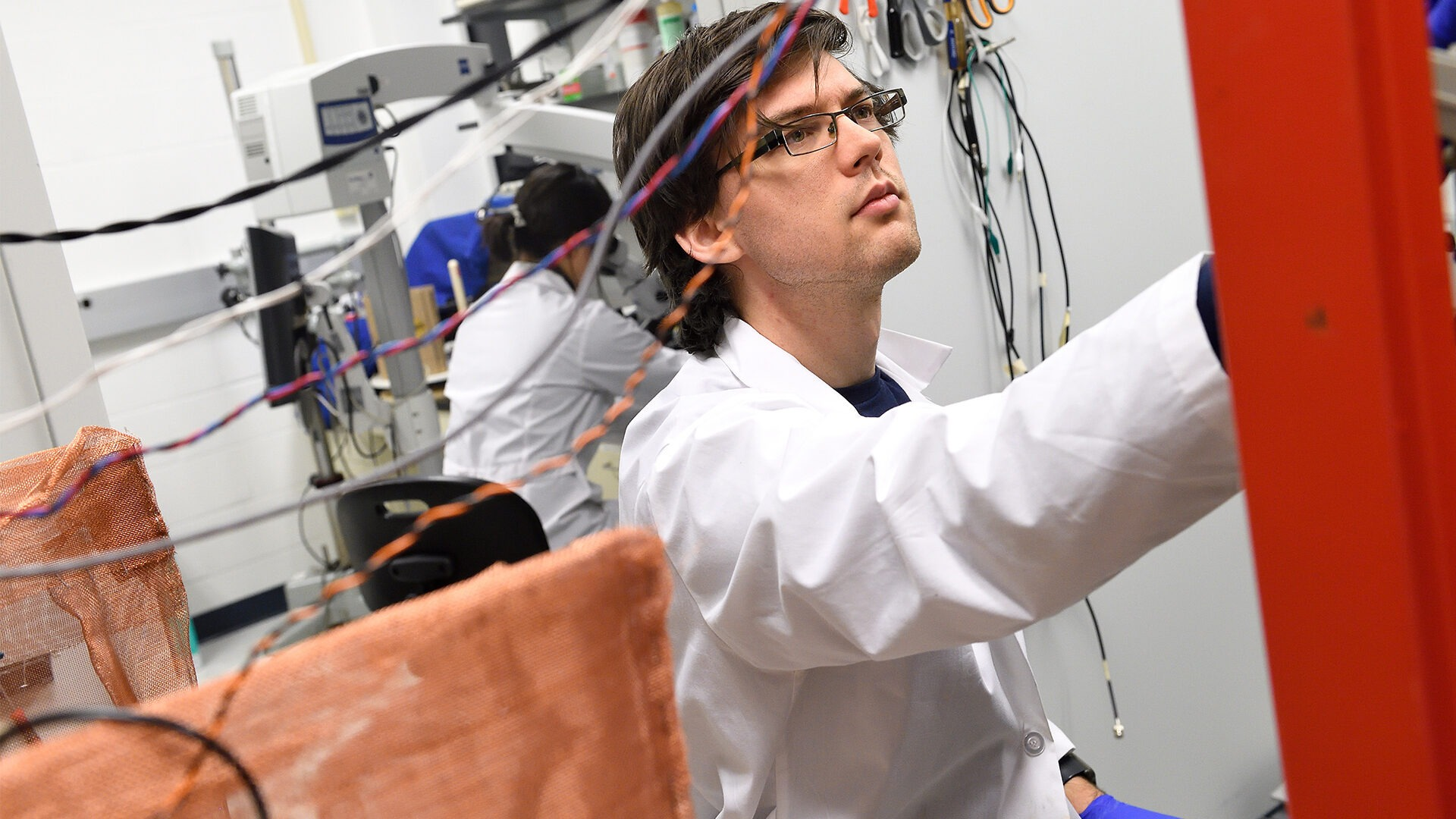 A male graduate student works in the lab amongst lots of wires.