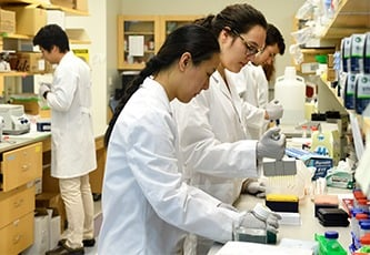 Two female students are wearing white coats and working in a wet lab.