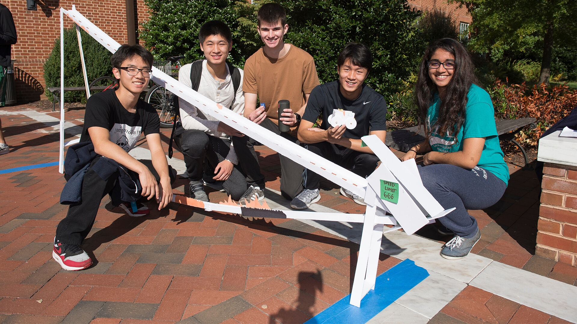 A group of students pose outside with their foam-core roller coaster design.