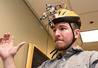 Student poses wearing a helmet prototype he and his teammates designed.