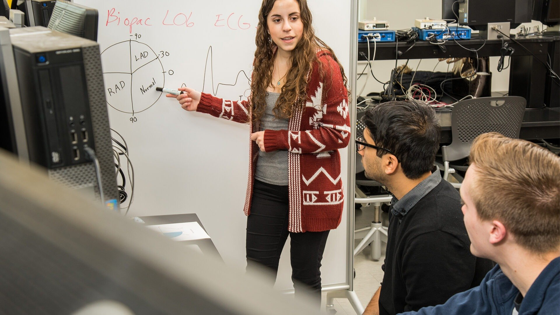 A female student stands at a whiteboard discussing something with two classmates.