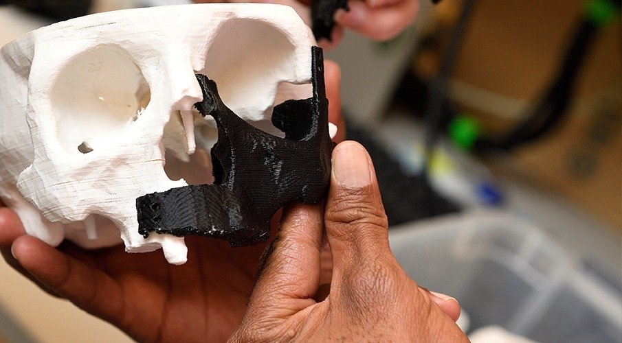 A set of hands hold up a 3-D printed human skull.