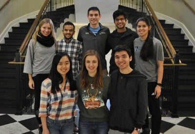A group of students stand in front of a curved staircase and smile at the camera.