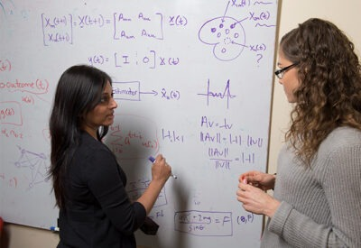 A faculty member and a student discuss equations at a white board.