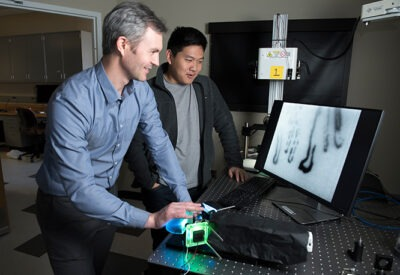 A student and faculty member are using an imaging device that projects images of the inner workings of the finger on a computer screen..