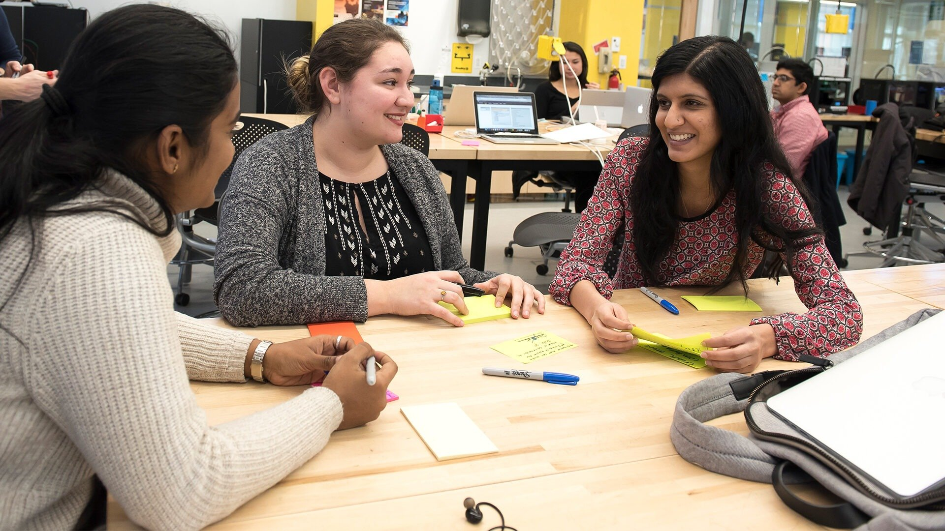Three female students sit at a table in the design studio and discuss something during class.