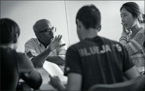 Tilak speaks with a group of students at a table.