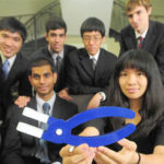 A group of students gather for a photo with their prototype.