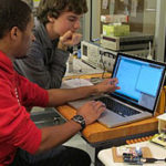 Two students work at a computer in the lab.