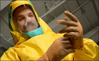 A man tries on the yellow ebola suit.