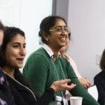 Young female researchers discuss career topics in a group.