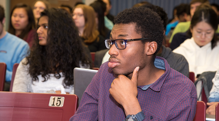 An African-American male student sits in a lecture hall and listens.