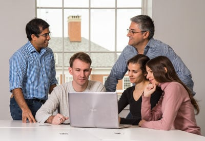 A group of students and faculty chat while working around a laptop.