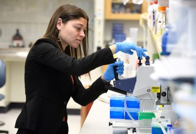 A young female faculty member works with pipettes in a wet lab.