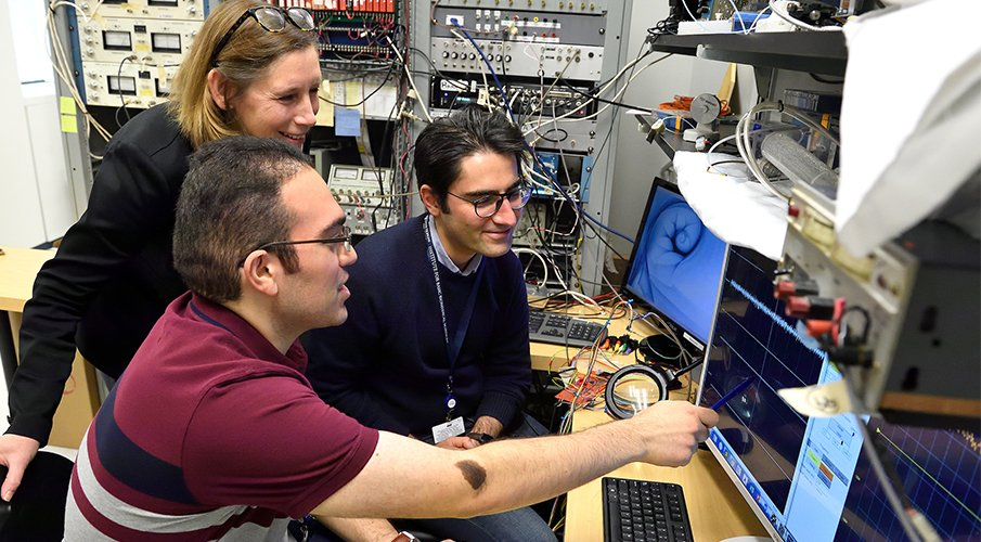 Two male students work at a computer with a female professor.