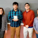 Three BME students stand with a teacher holding the piece of scrap metal.