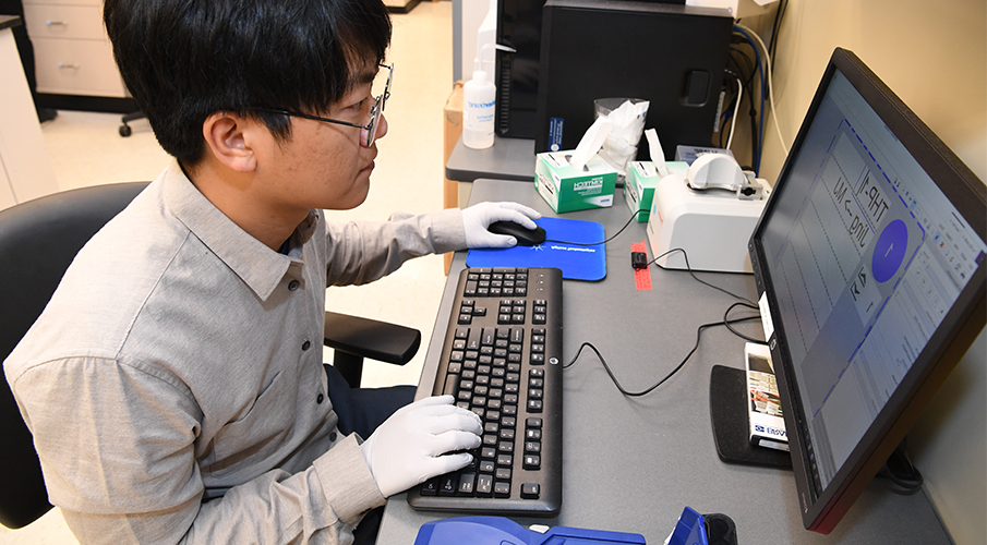 A male student works at a computer in a lab wearing gloves.