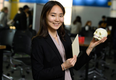 A female student holds a model of the human skull while smiling at the camera.