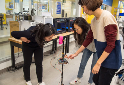 Three female students work in the Design Studio on their smart cane prototype.