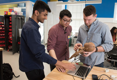Three male students work on their prototype with a doll and a laptop.
