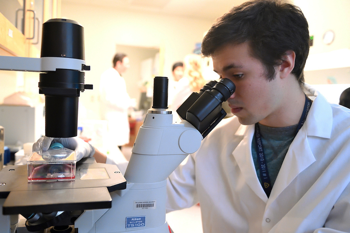 An student is wearing a white coat while he looks into a microscope.