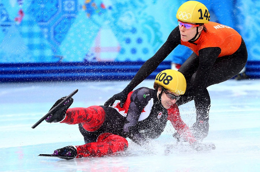 Two professional ice skaters are falling.