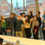 Josh Doloff and the students in his lab gather for a fun group photo in front of windows looking out onto the School of Medicine campus.