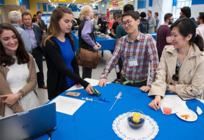 Two alumni talk to two students to discuss a prototype sitting on the table.