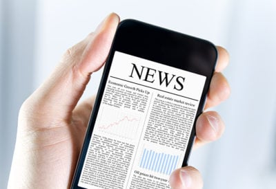 A hand holds a smartphone showing a digital newspaper.