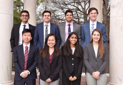 A group of students are dressed professionally and standing together in front of building.