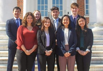 A group of students are dressed professionally and standing together on a set of outdoor stairs.
