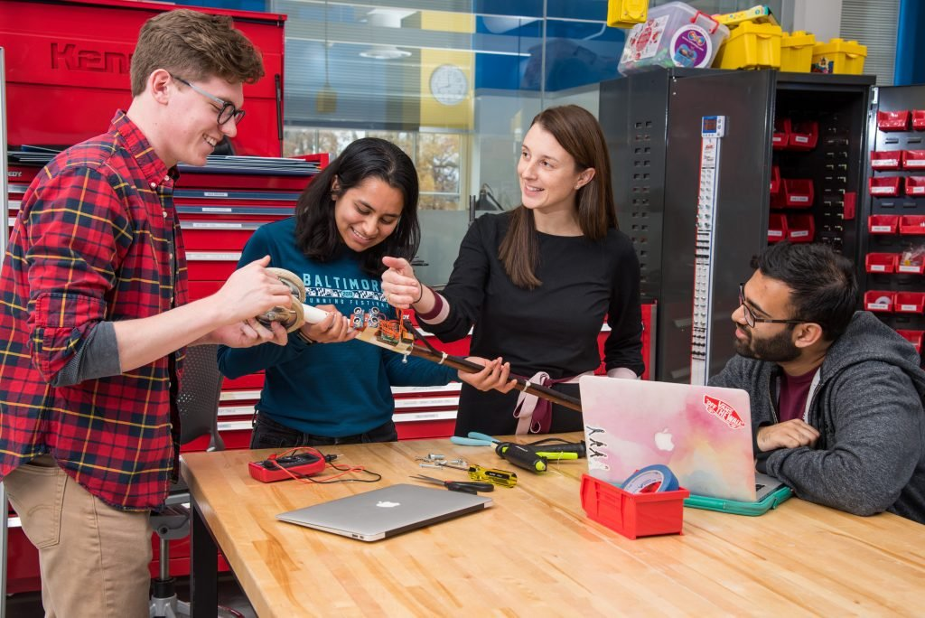 A group of students work with a faculty member on a prototype in the Design Studio.
