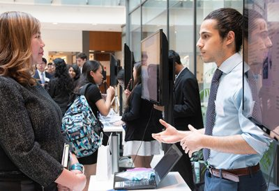 A student speaks with an industry partner in a large room.