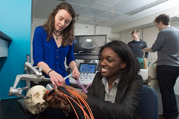 A female student works with a female faculty member on an imaging device and a skull model.