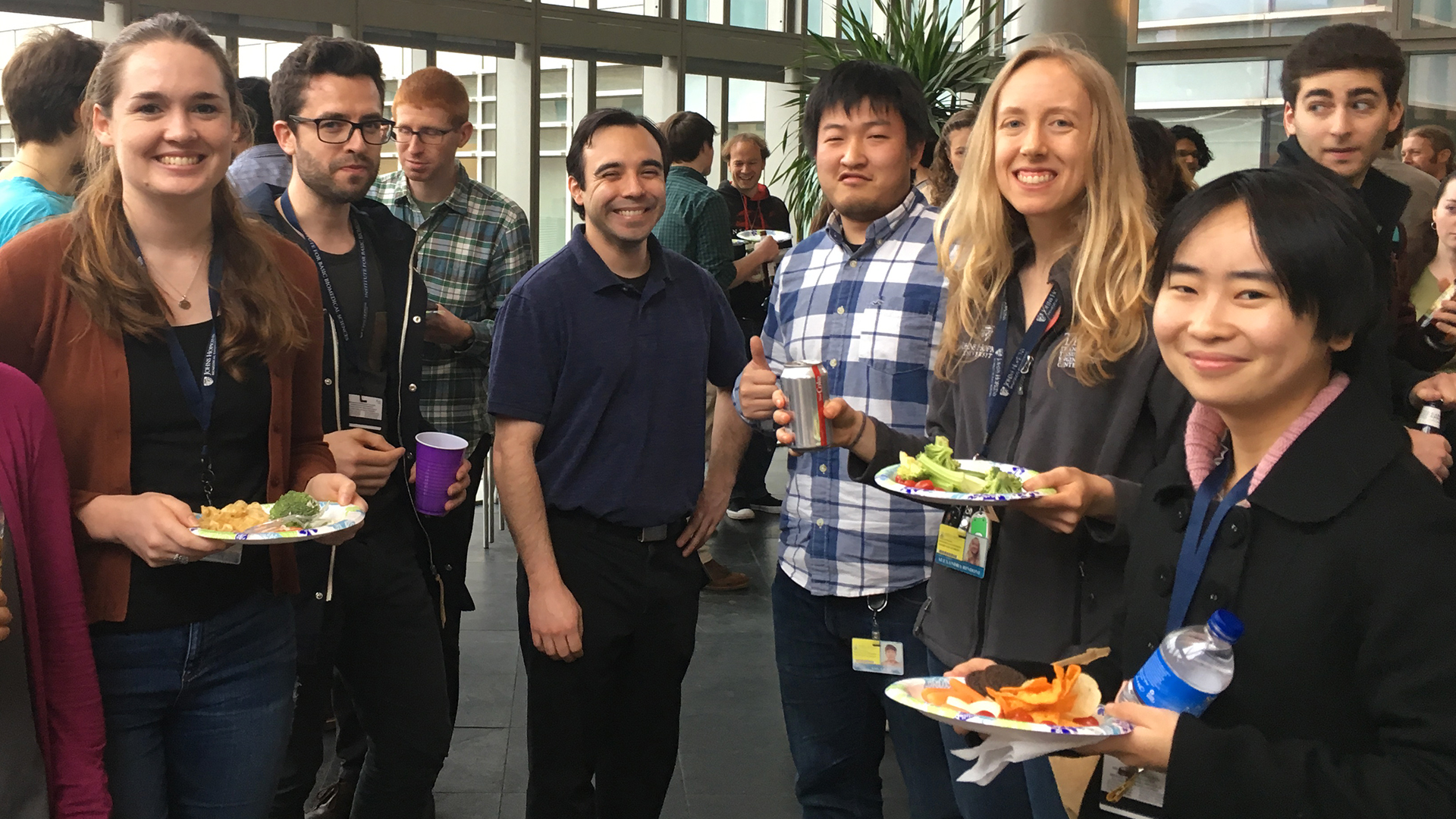 A group of graduate students are holding food and drinks and enjoying a social hour.