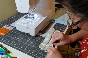 Ivy Wang is working at her sewing machine.
