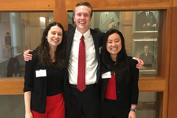 Three students stand together wearing a combination of red, white, and black clothing.