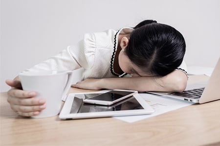 A woman is resting her head on her desk with a cup of coffee in her hand.
