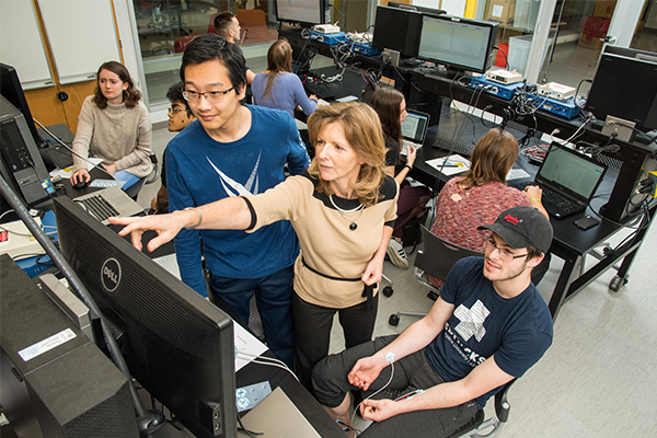 A female professor works with students in the computer lab.