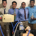 A group of four male students stand together with their breathing assistance prototype.