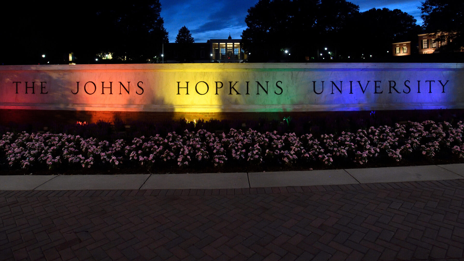 Colorful lights are shining on the Johns Hopkins University sign.