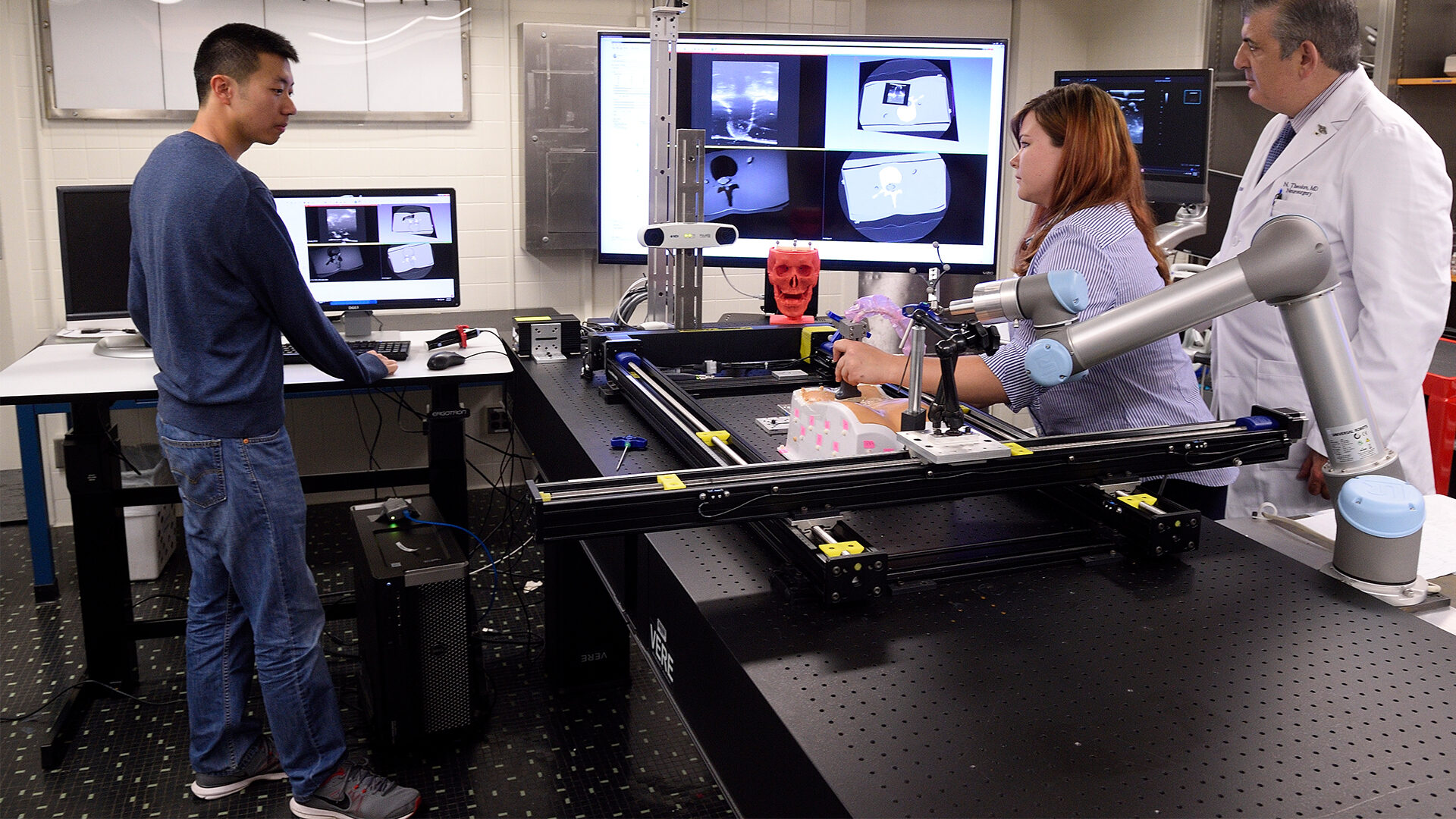 A wide shot of an imaging lab with three people working.