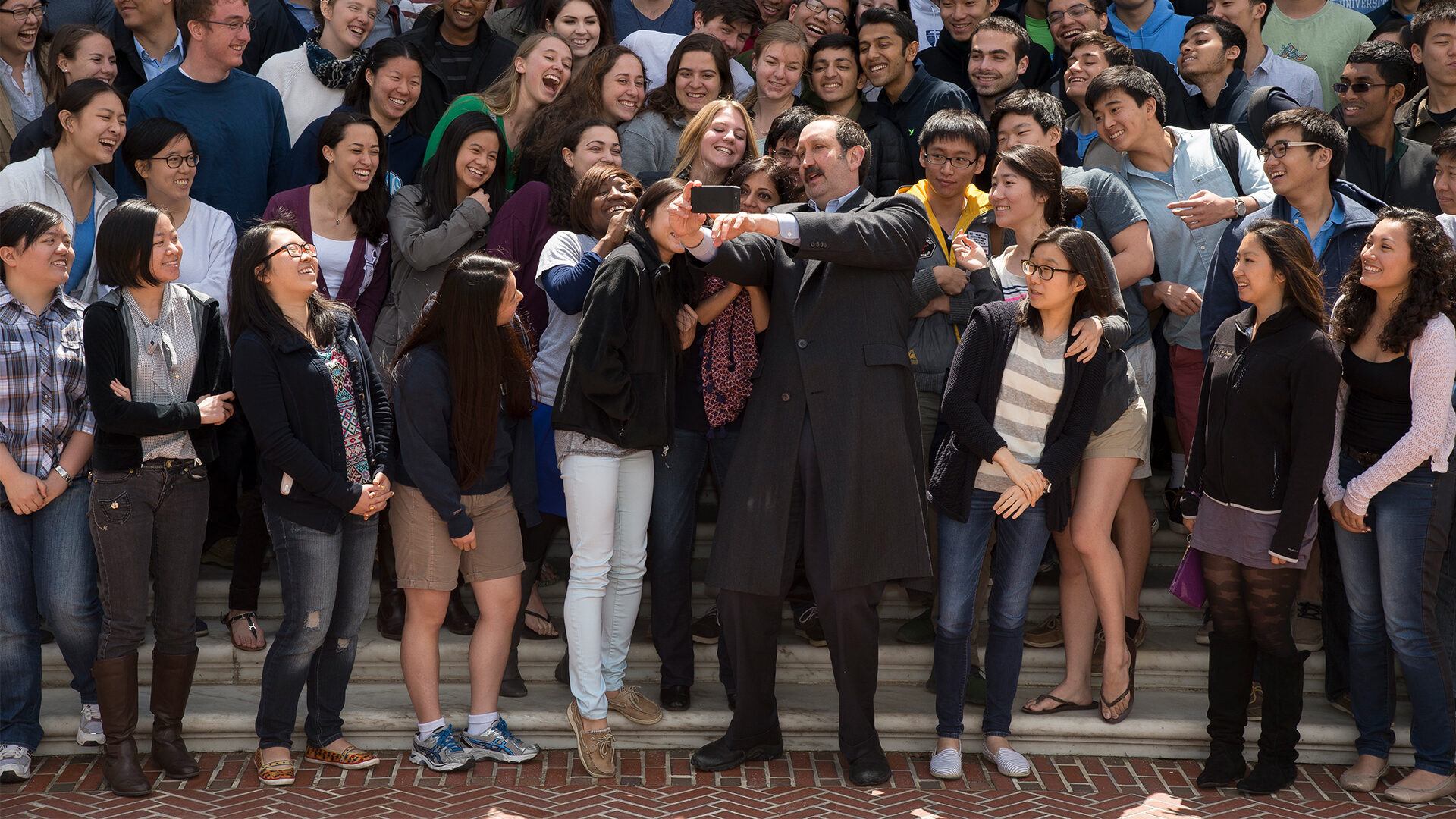 A large group of students take a selfie with a professor.