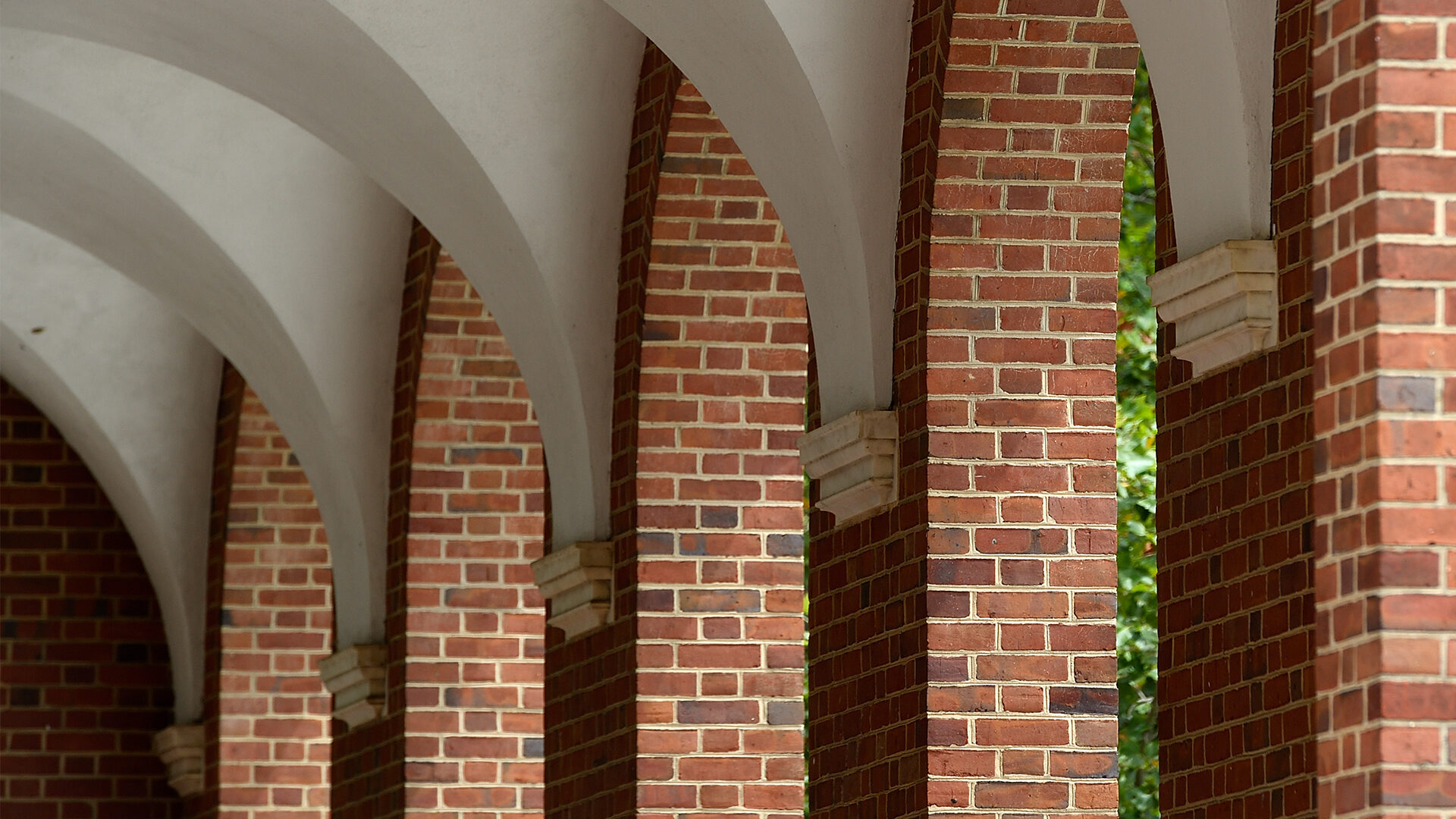 A shot on campus shows bring pillars and white arches.