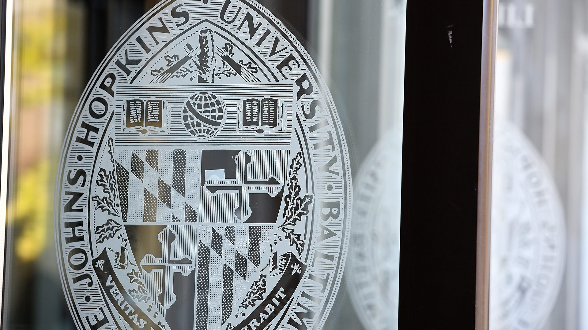 The JHU crest is shown on a glass door.