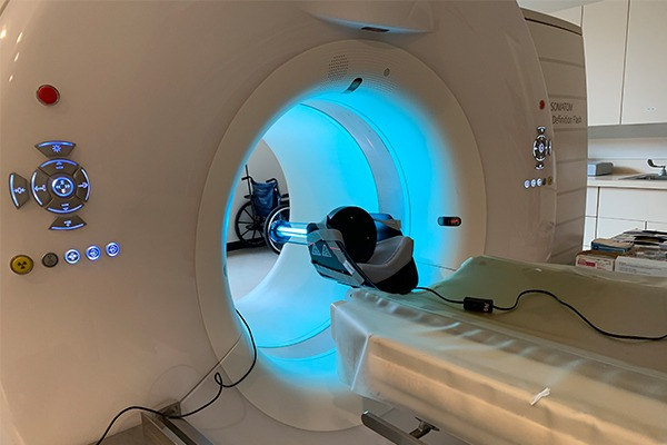 A CT scanner has a uv light shining on the inner bore.