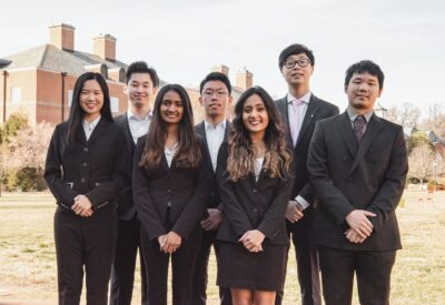 A group of students are dressed business professional and standing in a group.