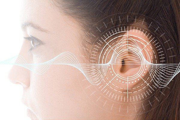 An image of a woman's ear is shown with white lines representing sound waves.