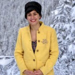 Alaleh Azhir is dressed in a yellow coat and black hat, and is standing in front of snow-covered trees.